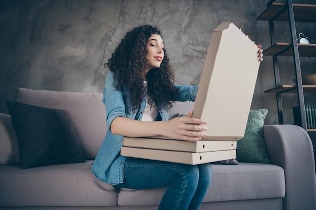 Fille assise sur le canapé tenant dans les mains des boîtes à tarte qui sent l'arôme intérieur de style industriel loft moderne
