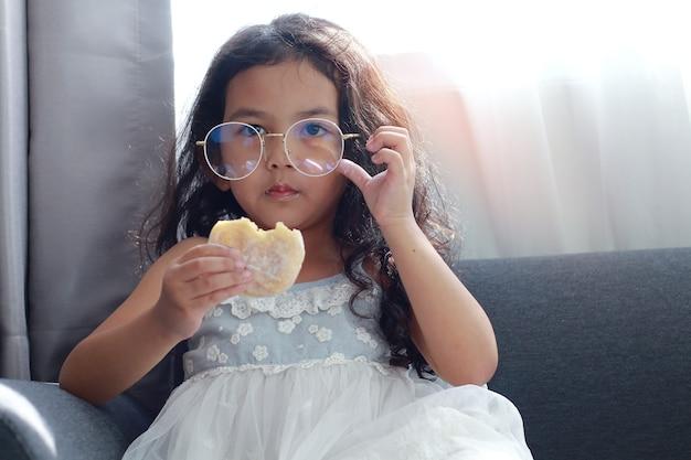 Fille assise sur le canapé en train de manger un beignet