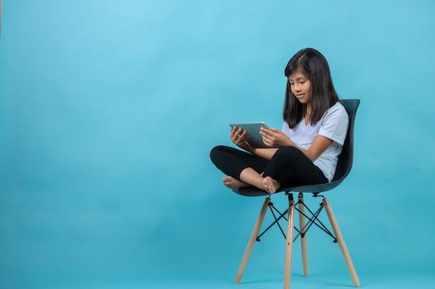 Fille assise sur une chaise en regardant la tablette
