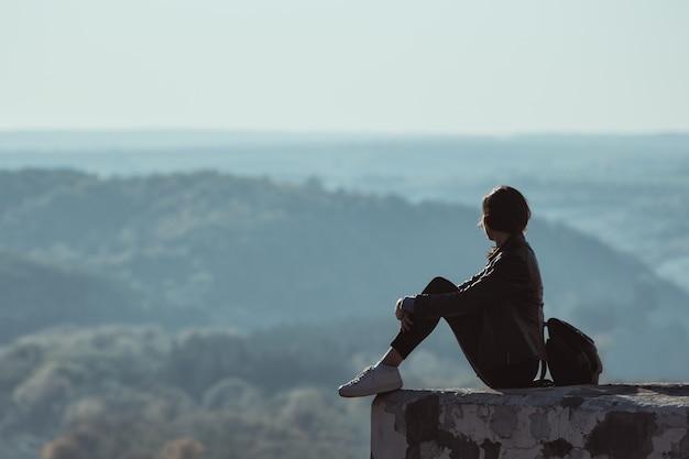 Fille assise sur la colline et regarde au loin dans la forêt. brume