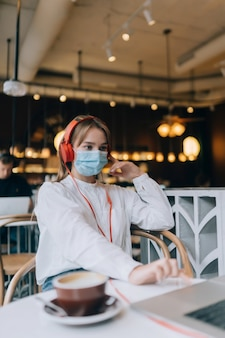 Une fille assise dans un café avec des écouteurs épidémie de coronavirus