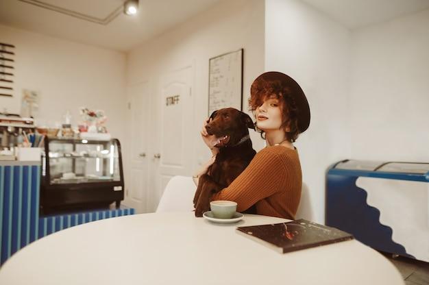 Fille assise dans un café lumineux avec un chien brun dans ses bras
