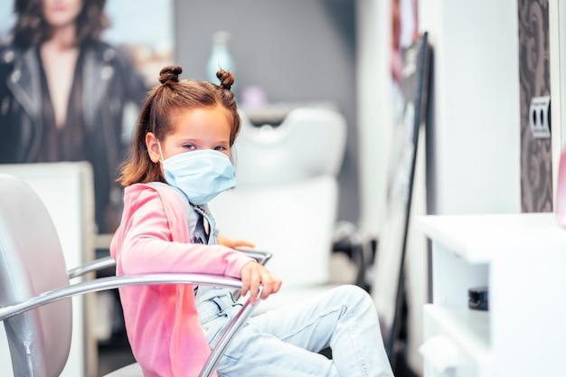 Fille assise dans le fauteuil de coiffure avec les nattes terminées. réouverture avec des mesures de sécurité pour les coiffeurs dans la pandémie de covid-19