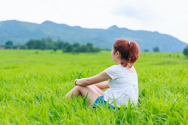 Fille assise dans une herbe des champs le matin