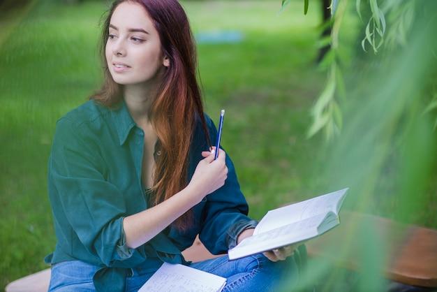 Fille assise dans un livre de parc