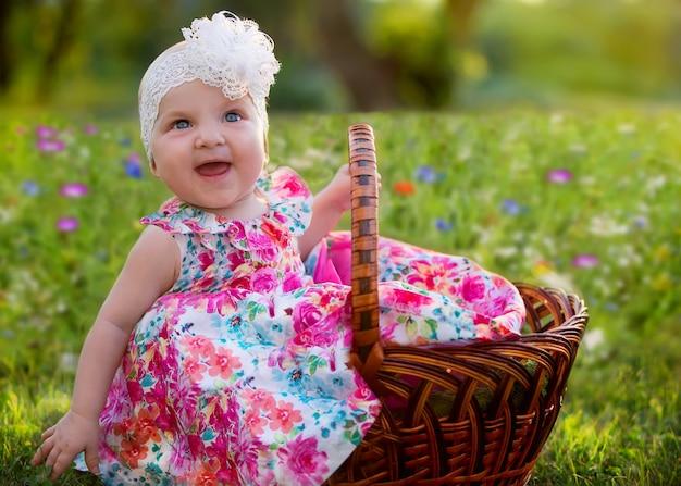 Fille assise dans un panier en osier et rit joyeusement sur un pré de fleurs