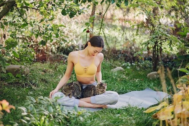 Fille assise dans un parc d'été avec chat mignon