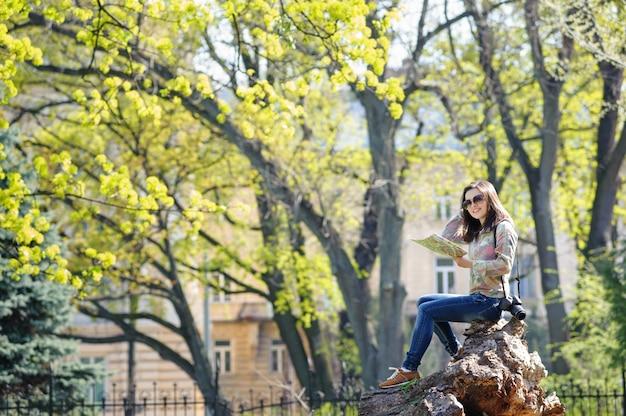 Fille assise dans le parc et lisant une carte