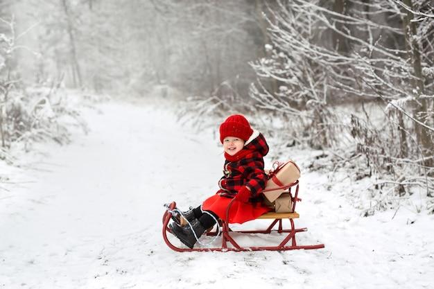 Une fille assise dans un traîneau dans les bois avec un tas de cadeaux de noël