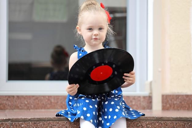 Fille assise avec des enregistrements sur les marches