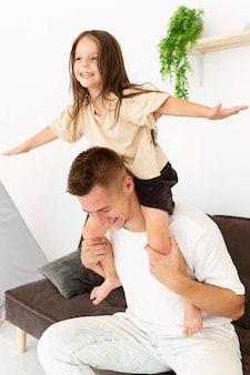 Fille assise sur les épaules de son père