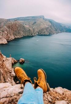 Fille assise sur la falaise devant la casse au-dessus de la mer