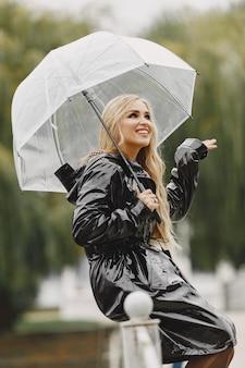 Fille assise. femme en manteau noir. blonde avec un parapluie.