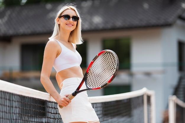 Fille assise sur le filet de tennis