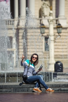 Fille assise à la fontaine avec carte et caméra montrant le chemin