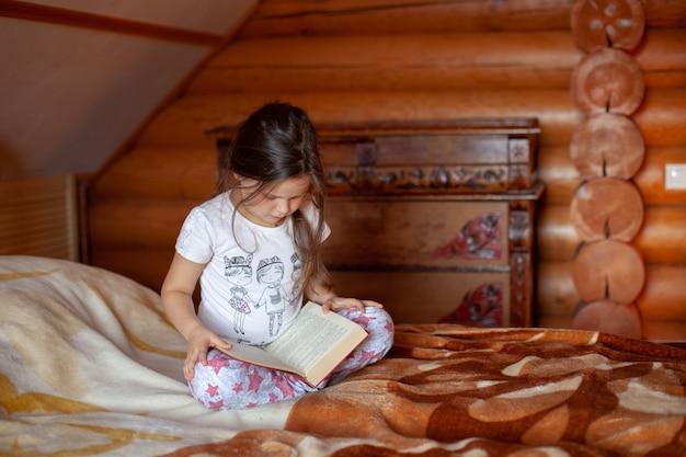 Fille assise les jambes croisées sur un lit et lit un livre dans la cabine og