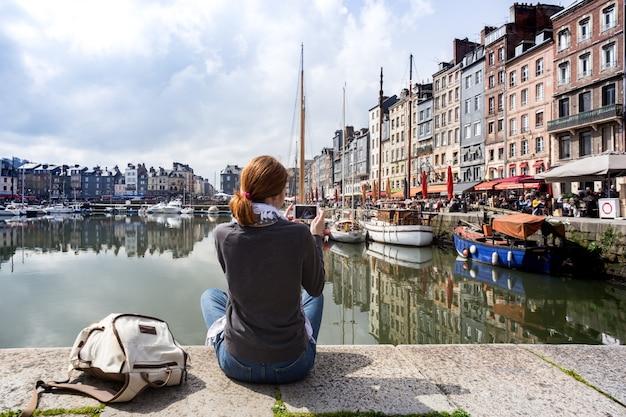 Fille assise sur une jetée et prenant une photo du port de honfleur avec son smartphone