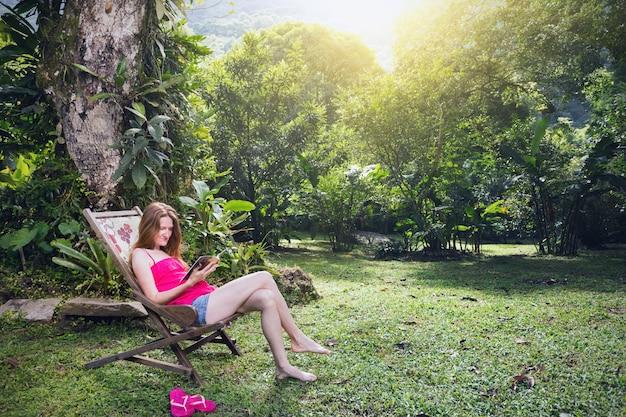 Fille assise lisant un livre dans une chaise longue dans un jardin tropical, brésil