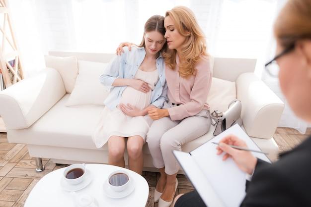 Fille assise avec maman sur le canapé et pleurer.