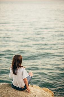 Fille assise sur une pierre au bord de la mer