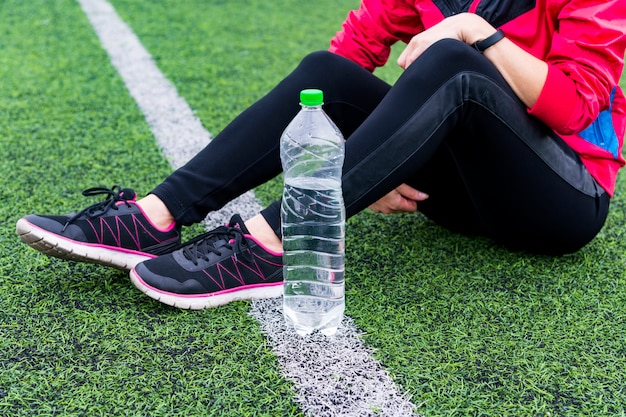 Fille assise sur la piste avec une bouteille d'eau