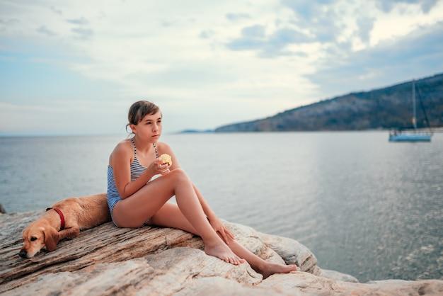 Fille assise sur la plage rocheuse avec chien et pomme à manger