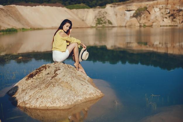 Fille assise près de la rivière