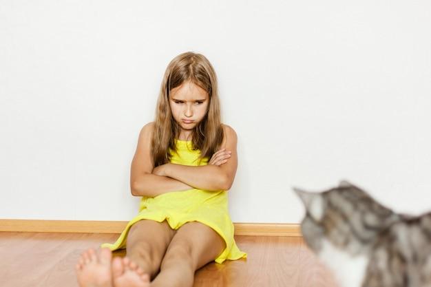 Fille assise sur le sol, bouleversée, offensée par le chat, animal de compagnie, rayé, main, pieds, robe jaune, bébé, famille, soins aux animaux