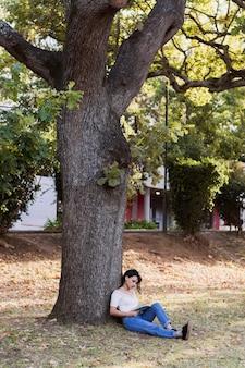 Fille assise sous un arbre