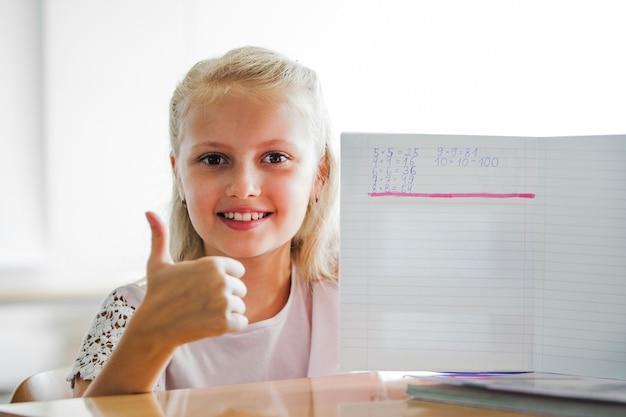 Fille assise à la table de l'école avec un cahier
