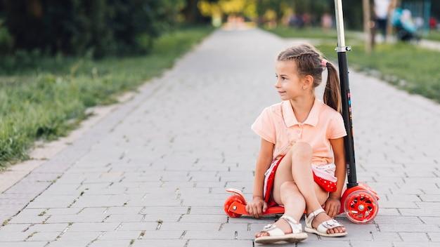 Fille assise sur un trottinette sur la passerelle droite