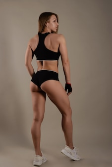 Fille athlétique avec une belle silhouette se tient avec son dos au public