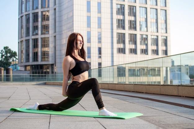 Fille athlétique faisant du yoga le matin dans la rue, elle s'étire sur la ville, la femme fitness s'entraîne sur le tapis