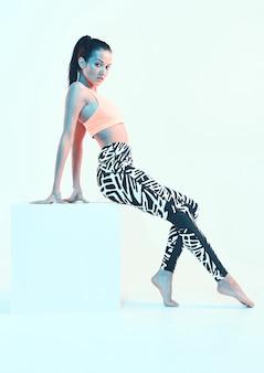 Fille athlétique posant dans des vêtements de sport en néon sur cube. modèle ajusté avec des formes corporelles parfaites