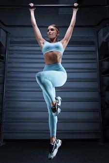 Fille athlétique tire sur la barre dans la salle de gym sur un fond bleu. le concept de sport, fitness, aérobic, musculation, stretching.