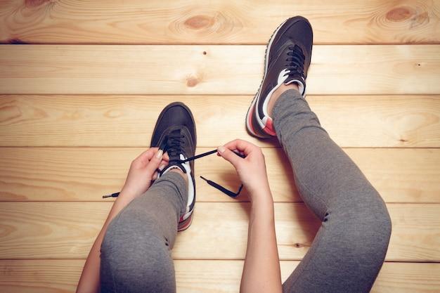 Fille attachant les lacets assis sur le plancher en bois. vue de dessus