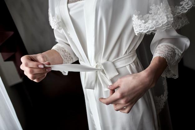 Une fille attache une ceinture sur sa robe debout près de la fenêtre, une femme se prépare avant la cérémonie de mariage