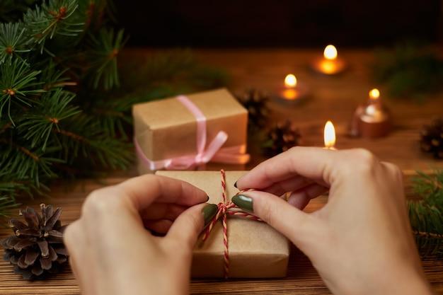 La fille attache la corde sur la boîte-cadeau sur fond de branches de sapin, de cônes et de bougies allumées