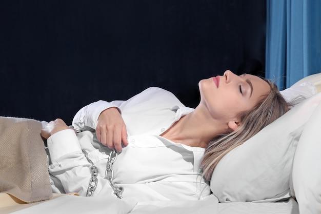 Fille attachée avec une chaîne au lit. notion de paralysie du sommeil