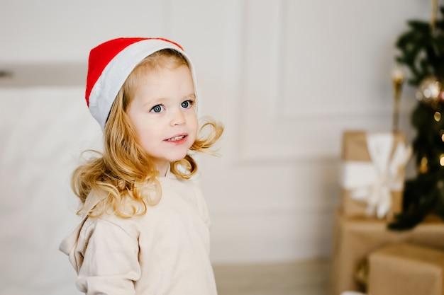 Fille attend les cadeaux du nouvel an près de l'arbre de noël. fille de bébé drôle en attente de surprise.
