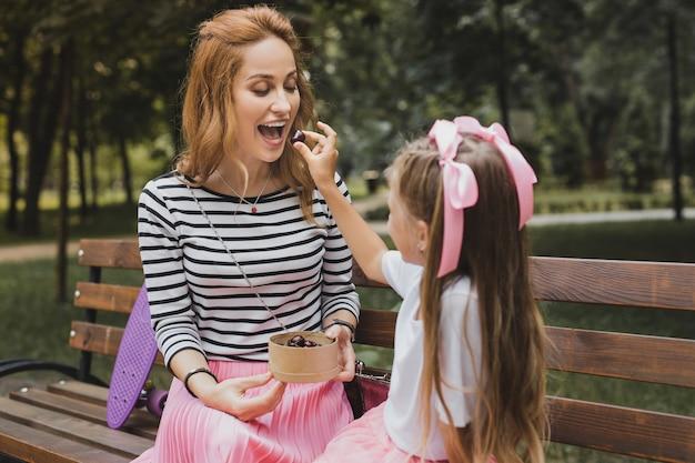 Fille attentionnée. une jolie fille aux cheveux blonds qui donne des bonbons à sa mère tout en passant le week-end en plein air