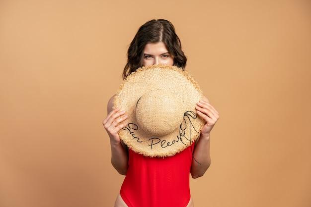 La fille attirante couvre son visage avec un chapeau de paille