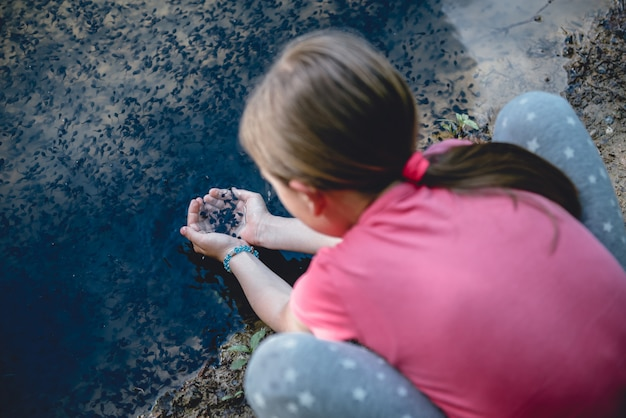 Fille au bord du lac attraper un têtard