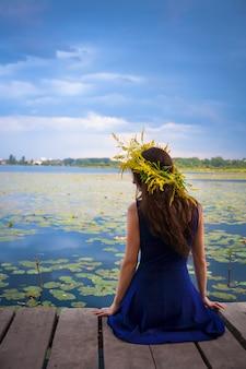Fille au bord du lac avec une couronne sur la tête
