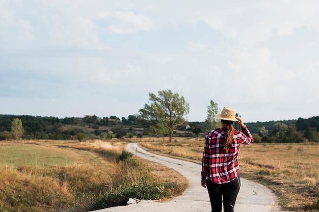 Fille au bord d'une route de campagne