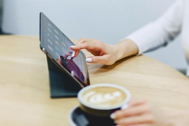 Fille au café boit du café et travaille sur tablette