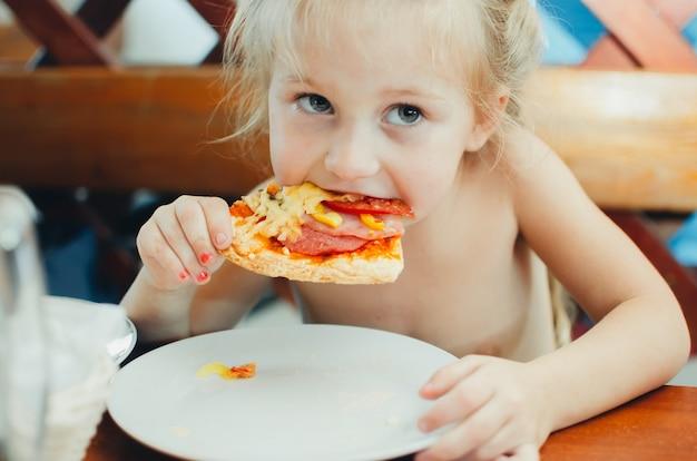 La fille au café mangeant une pizza avec des saucisses
