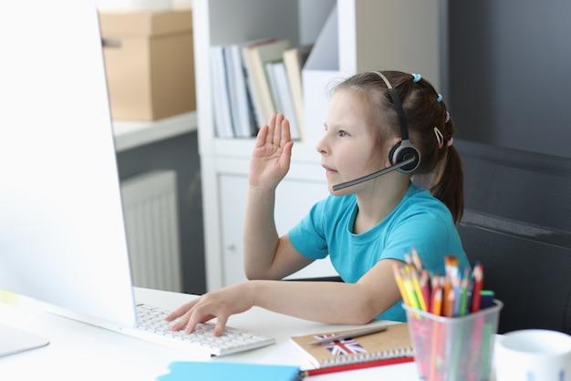 Une fille au casque est assise devant un écran d'ordinateur et étend ses bras pour répondre en lesso en ligne