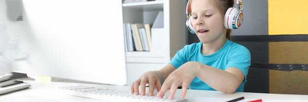 Une fille au casque est assise devant un écran d'ordinateur et tape sur le clavier
