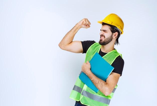 Fille au casque jaune tenant un dossier bleu et montrant un signe de plaisir.